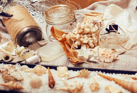 Viele Meeresthemen in Chaos wie Muscheln, Kerzen, Parfüm, Mädchensachen auf Leinen, hübsche strukturierte Postkartenansicht Vintage Nahaufnahme Standard-Bild