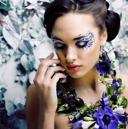 floral face art with anemone in jewelry, sensual young brunette woman in studio