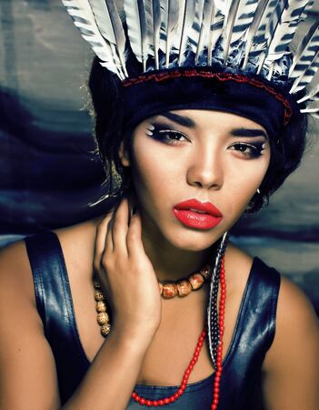 young pretty woman with make up like red indian, futher in hair, fashion hallowen concept Banco de Imagens