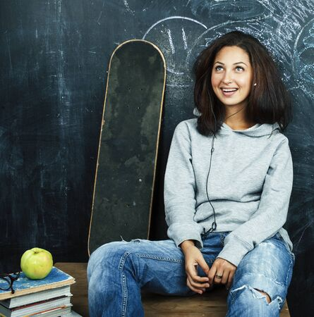 young cute teenage girl in classroom at blackboard seating on table smiling, modern hipster concept Stock fotó