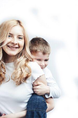 귀여운 아들과 함께 젊고 현대적인 금발 곱슬머리 어머니는 흰색 배경, 라이프스타일 사람들 개념, 자매 및 형제 친구에 쾌활한 포즈를 취하는 행복한 웃는 가족 스톡 콘텐츠