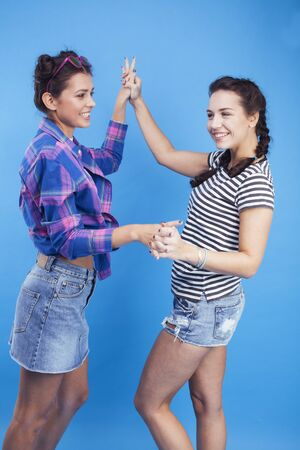 lifestyle people concept: two pretty young school teenage girls having fun happy smiling on blue background Фото со стока