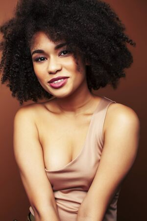 pretty young african american woman with curly hair posing cheerful gesturing on brown background, lifestyle people concept Archivio Fotografico - 138552363