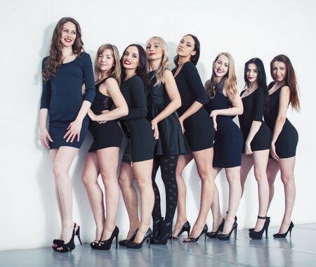Beaucoup de femmes diverses en ligne, vêtues de petites robes noires fantaisie, maquillage de fête, style de vie concept de vice-escouade