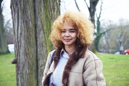 Joven linda rubia estudiante afroamericana sonriendo en el parque verde, concepto de pueblo de estilo de vida