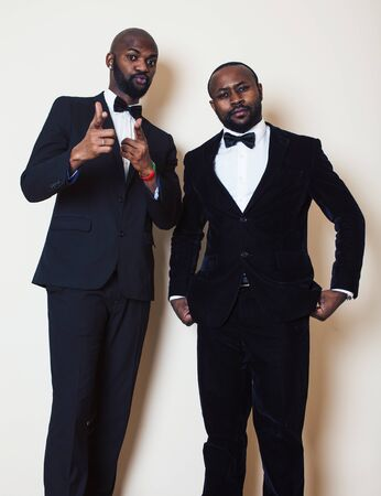 two afro-american businessmen in black suits emotional posing, gesturing, smiling. wearing bow-ties entertaiment stuff Stock Photo