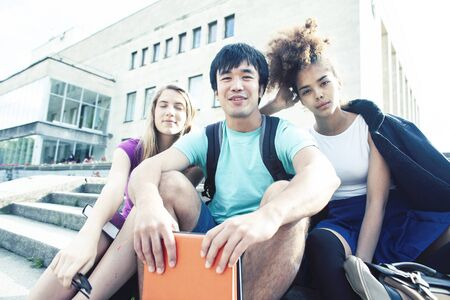 cute group of teenages at the building of university with books huggings, diversity nations real students lifestyle