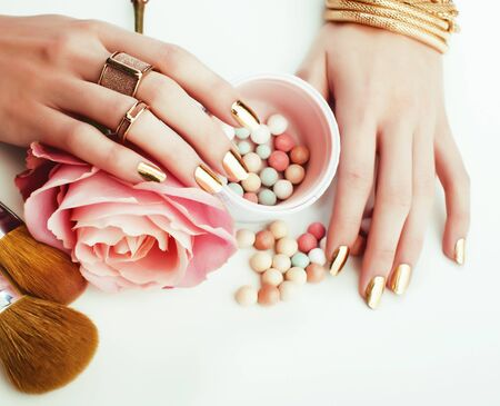 woman hands with golden manicure and many rings holding brushes, makeup artist stuff stylish, pure close up pink flower rose among cosmetic for makeup 스톡 콘텐츠