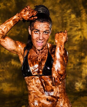 young brunette girl on bright background covered chocolate cream all over her body and face, lifestyle people concept