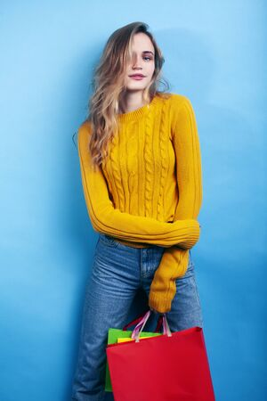 young pretty teenage modern hipster girl posing emotional happy on blue background, lifestyle people concept Reklamní fotografie