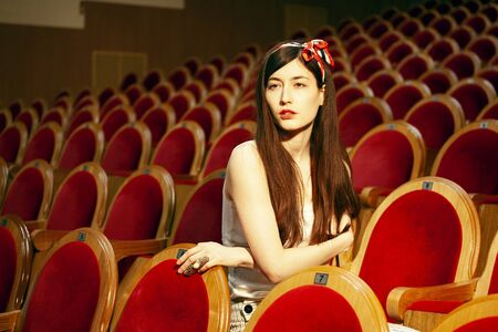 portrait of a pretty girl hipster in a movie theater posing in fashion style, dreaming alone Banque d'images