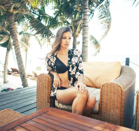 young pretty woman at swimming pool relaxing in chair, fashion look in lingerie at hotel, lifestyle people concept