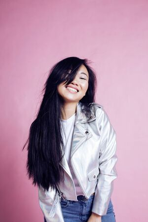 young pretty smiling asian korean girl wearing modern fashion clothers on pink background, lifestyle people concept