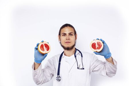 young pretty doctor with stethoscope holding fruits, healthy food care concept Reklamní fotografie