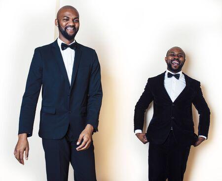 two afro-american businessmen in black suits emotional posing, gesturing, smiling. wearing bow-ties entertaiment stuff Reklamní fotografie