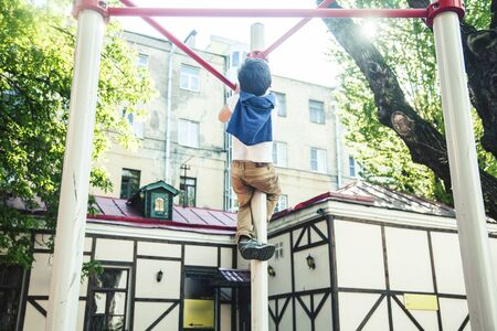 little cute blond boy hanging on playground outside, alone training with fun, lifestyle children concept Reklamní fotografie
