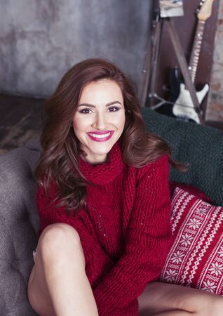 young pretty stylish woman in red winter sweater at couch in home interior happy smiling, lifestyle people concept