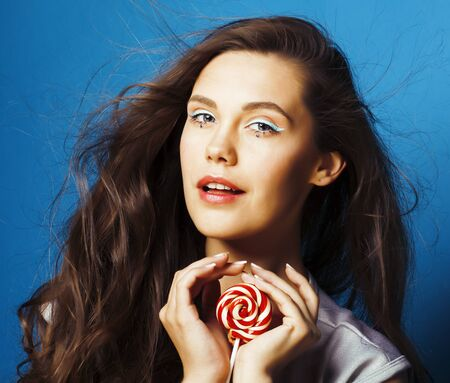 young pretty adorable brunette woman with candy close up posing on blue background, like doll makeup, fashion beauty people concept Zdjęcie Seryjne
