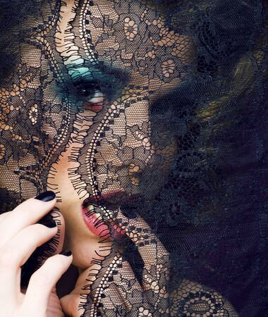 portrait of beauty young woman through lace close up mistery makeup sexy, fashion people concept Banco de Imagens