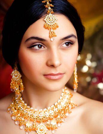 Schönheit süßes echtes indisches Mädchen in Sari lächelnd auf schwarzem Hintergrund, Schmuck glänzend