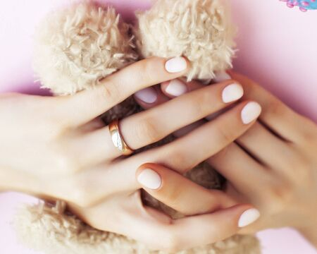 woman hands with manicure wearing wedding ring holdind teddy bear and macaroons on pink background closeup Foto de archivo