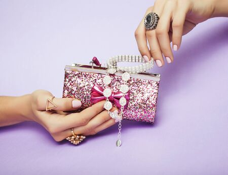 little girl stuff for princess, woman hands holding small cute handbag with jewelry and manicure, luxury lifestyle concept closeup