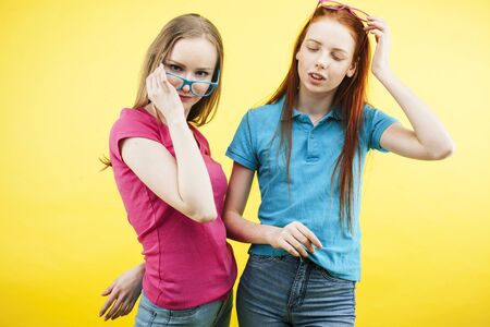 lifestyle people concept: two pretty young school teenage girls having fun happy smiling on yellow background wearing glasses Stock fotó