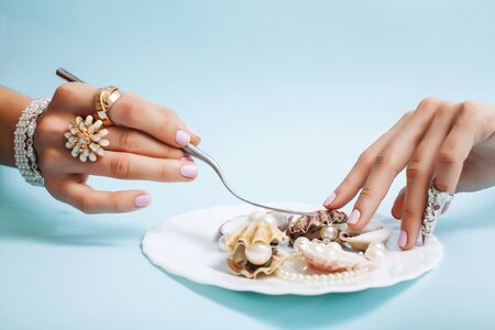 beautiful woman hands with pink manicure holding plate with pearls and sea shells, luxury jewelry concept closeup