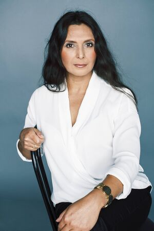 hübsche Brünette selbstbewusste reife Frau sitzt auf einem Stuhl im Studio, Lifestyle-Menschen-Konzept Standard-Bild