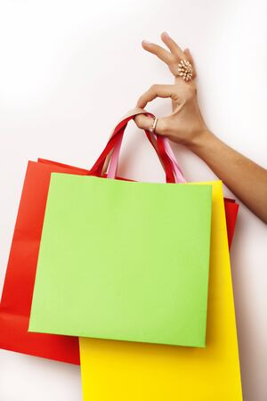 woman hand holding few paper bags on white background isolated, shopping sale concept close up