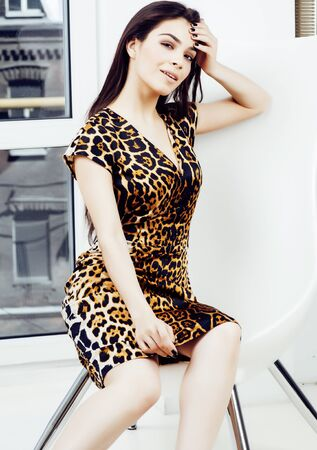 pretty stylish woman in fashion dress with leopard print in luxury house interior, lifestyle people concept Stock Photo