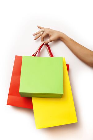 woman hand holding few paper bags on white background isolated, shopping sale concept