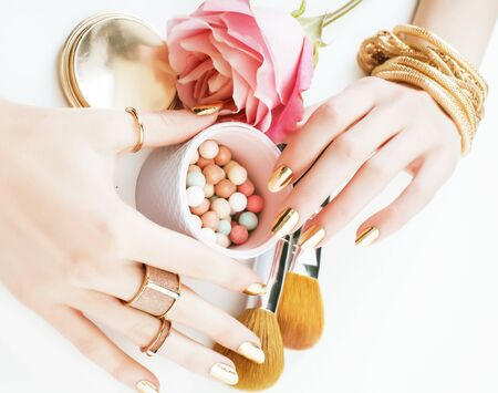 woman hands with golden manicure and many rings holding brushes, makeup artist stuff stylish, pure close up pink flower rose among cosmetic for makeup