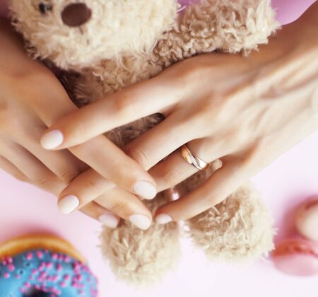 woman hands with manicure wearing wedding ring holdind teddy bear and macaroons on pink background closeup 版權商用圖片