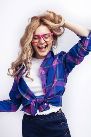 young pretty blond teenage hipster girl in glasses posing emotional happy smiling, gesturing isolated on white background, lifestyle poeple concept