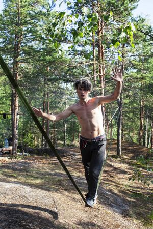 young man doing slackline rodeo in forrest outside sports activities, lifestyle people concept