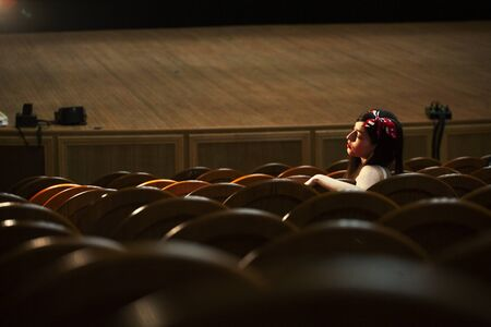 portrait of a pretty girl hipster in a movie theater wearing hat, dreaming alone, fashion lufestyle people concept
