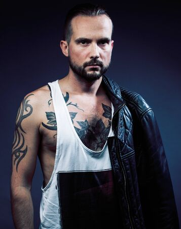 A man with tattooes on his arms. Silhouette of muscular body. caucasian brutal hipster guy with modern haircut, looking like criminal close up