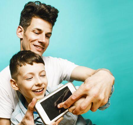 junges hübsches Mannmodell mit kleinem süßen Sohn, der zusammen spielt, modernes Menschenkonzept des Lebensstils, Familienmännchen