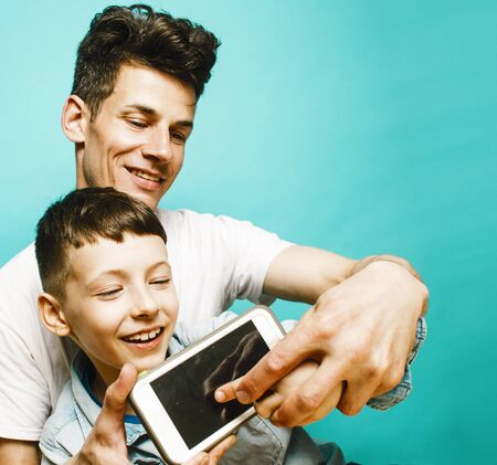 young pretty man model with little cute son playing together, lifestyle modern people concept, family male