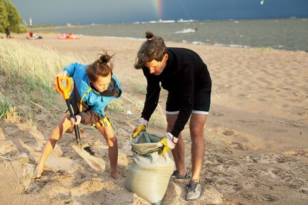 young father with son on beach digging pit under the rainbow, playing, looking for treasure, lifestyle happy family on vacation closeup