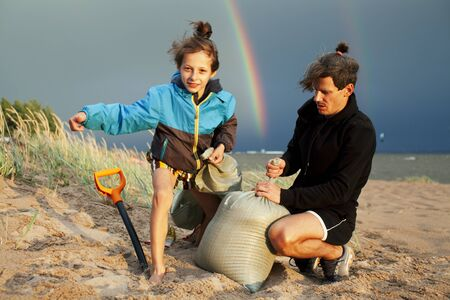 young father with son on beach digging pit under the rainbow, playing, looking for treasure, lifestyle happy family on vacation