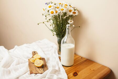 Simply stylish wooden kitchen with bottle of milk and glass on table, summer flowers camomile, healthy foog moring concept