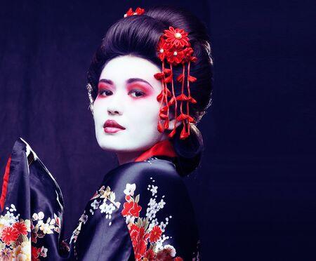 jeune jolie vraie geisha en kimono avec sakura et décoration sur fond noir