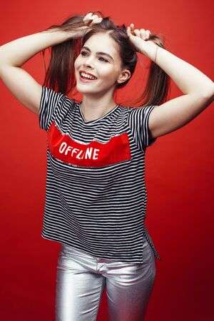 young pretty emitonal posing teenage girl on bright red background, happy smiling lifestyle people concept Zdjęcie Seryjne