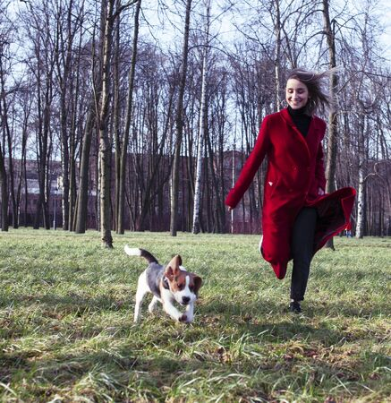 pretty young girl in redd coat playing with dog outside in green park, lifestyle people concept Фото со стока