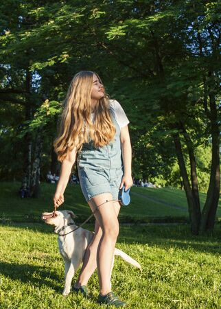 young attractive blond woman playing with her dog in green park at summer, lifestyle people concept Archivio Fotografico - 147918775