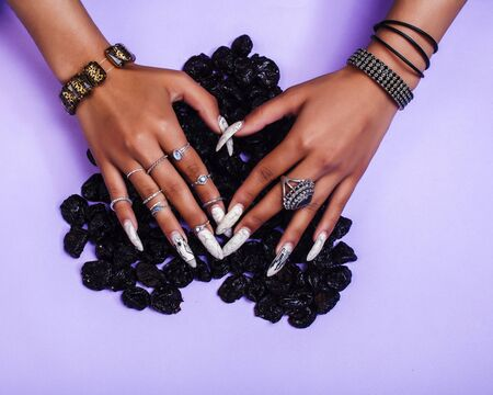 woman hands with long nails manicure holding dry fruits in shape of heart on purple background