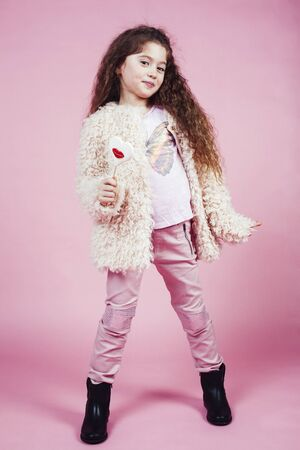 little cute girl with candy on pink background posing emotional, lifestyle people concept