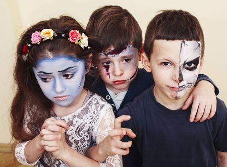 zombie apocalypse kids concept. Birthday party celebration facepaint on children dead bride, scar face, zombie skeleton together closeup makeup emotional posing.